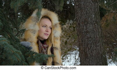 Beautiful young model participating in a photo shoot in the woods in winter. She looks at the camera smiling. Slow motion