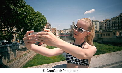 Beautiful young model smiling and making selfie in historical center.