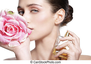 Beautiful young model spraying a flowers fragrance on her...