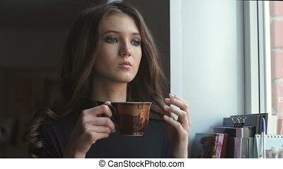Beautiful young model standing next to the window and drinking coffe.