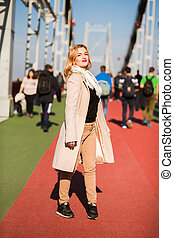 Beautiful young model wears beige coat and white scarf, posing in sunny day