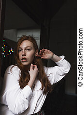 Beautiful young model with freckles on a garlands background