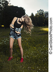 Beautiful young model with hair in motion posing at the park