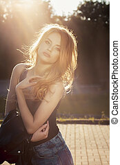 Beautiful young model with lush wave hair posing in rays of sun