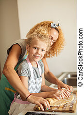 Beautiful young mom and her cute little daughter rolling out dough at home.