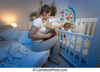 Beautiful young mother and baby boy in crib at night