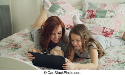 Beautiful young mother and her cute daughter in pajamas...
