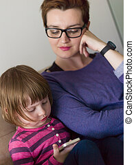 mother and her cute little daughter are using a mobile phone