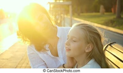 Beautiful young mother and her daughter have fun in the park. Mother takes care of her daughter, straightens her hair at sunset. Slow motion
