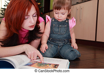beautiful young mother and her little daughter in denim jumpsuit reads book
