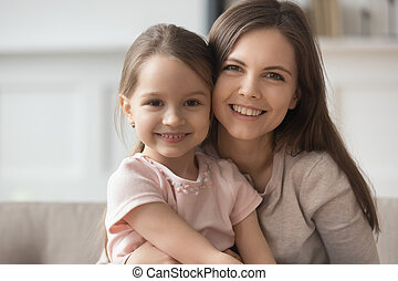 Beautiful young mother and little daughter bonding looking at camera