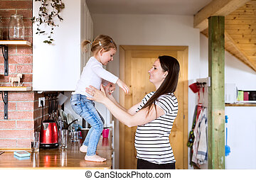 Beautiful young mother and little daughter in the kitchen.
