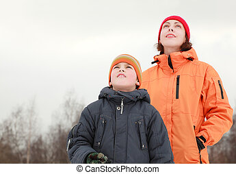 beautiful young mother and little son looking in sky at winter outdoors, focus on boy
