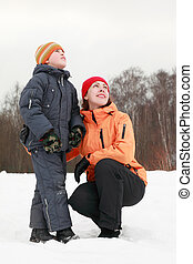 beautiful young mother and little son standing at snow and looking in sky at winter outdoors; focus on woman