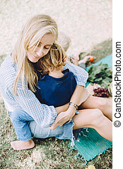Beautiful young mother hugging her little son sitting on ground outdoor