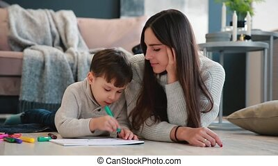 Beautiful young mother in a warm sweater lying on the floor with my son drawing with markers on paper portraying his family. The child learns to draw.