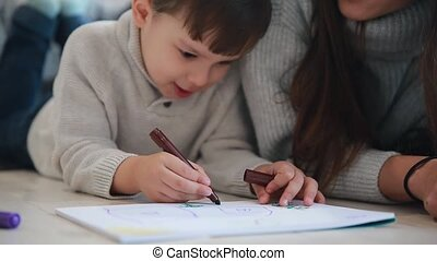 Beautiful young mother in a warm sweater lying on the floor with my son drawing with markers on paper portraying his family. The child learns to draw. Close-up