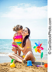 Beautiful young mother in swimsuit and a small 3 year daughter with a multi-colored pinwheel rainbow on the sandy beach at sea. Family love and kisses