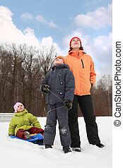 beautiful young mother, little son and daughter standing on snow and looking at sky in winter outdoors, focus on boy