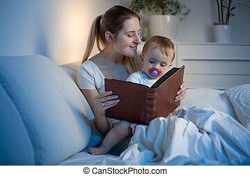 Beautiful young mother reading book to her baby before going to sleep