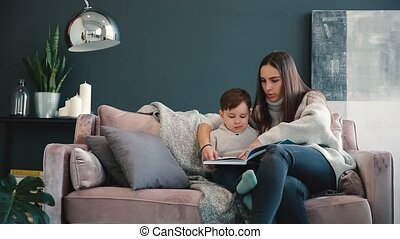 Beautiful young mother sitting on the sofa in your house the living room reads son a story in the ear and learn to read little boy.