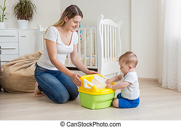 Beautiful young mother teaching her 10 months old son using ...