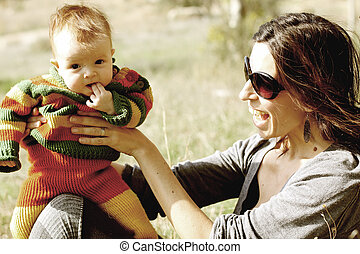 beautiful young mother with cute baby outdoor