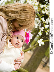 Beautiful young mother with her baby daughter in a garden