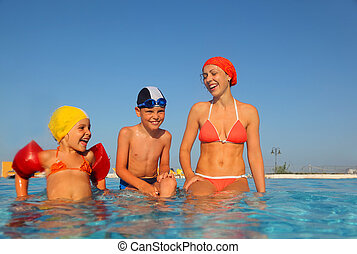 beautiful young mother with little son and daughter sitting in water in pool. from the underwater package