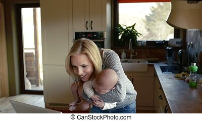 Beautiful young mother with son in the arms, working on laptop