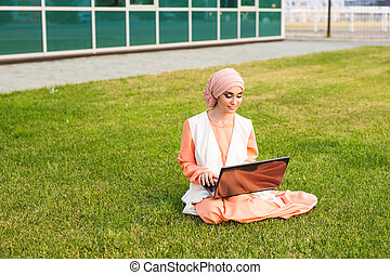 beautiful young Muslim girl sitting with notebook.