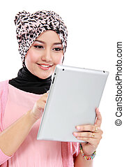 Beautiful young muslim woman using digital tablet computer