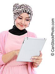 Beautiful young muslim woman using tablet computer