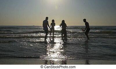 Beautiful young people having fun and dancing in the sea in...