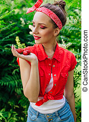 Beautiful young pin up girl with bright make up and fresh natural strawberry.
