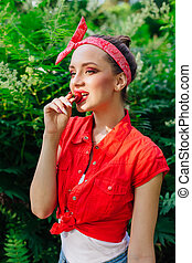 Beautiful young pin up girl with bright make up eating fresh natural strawberry.