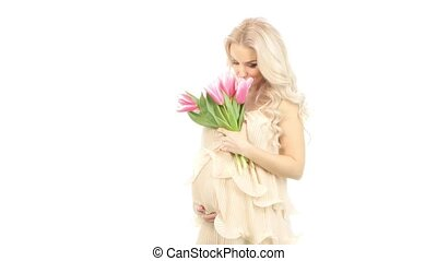 Beautiful young pregnant woman dressed in a pink dress with tulips, white
