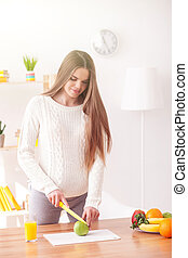 Beautiful young pregnant woman is preparing breakfast