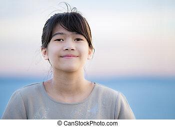 Beautiful young preteen girl enjoying outdoors by lake at sunset