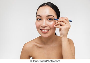Beautiful young pretty asian woman with healthy skin posing isolated over white wall background holding eye pencil.