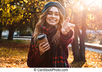 Beautiful young pretty woman walking outdoors in autumn spring park.