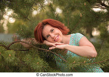 Beautiful young red hair woman in blue dress posing with a pine branch.