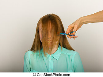 Beautiful young red-haired girl at the hairdresser makes blow drying, shorn bangs, hair polishing