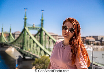 Beautiful young red-haired girl in a summer Cotton dress is photographed, looking at the camera on a sunny summer day in Budapest
