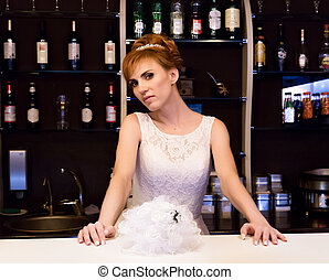 Beautiful young redhead bride wearing white wedding dress with professional make-up and hairstyle standing at bar