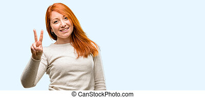 Beautiful young redhead woman raising fingers, number two isolated over blue background