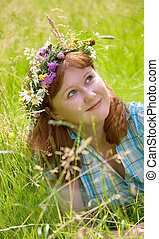 Beautiful young redheaded woman in a flower wreath