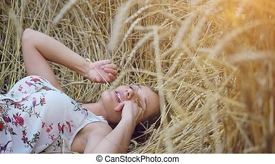 Beautiful young romantic woman with long hair lies on wheat Field in slowmotion. 1920x1080