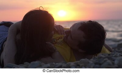 Beautiful young romantically lay on the shore under the sun...