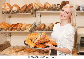 Beautiful young saleswoman is working in bakery